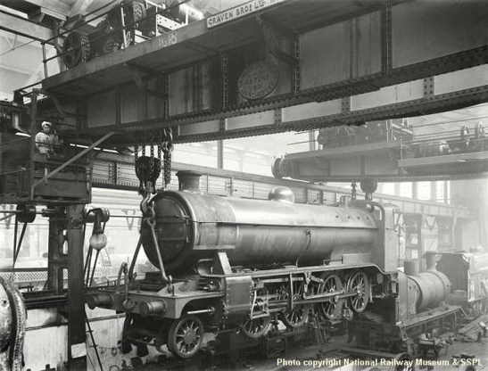A pair of overhead cranes are lifting a newly-built Great Northern Railway O2 Class 2-8-0 locomotive in the erecting shop at Doncaster Works on 14th December 1919. The cranes, built by Craven Brothers of Manchester in 1901, could each lift 35 tons.